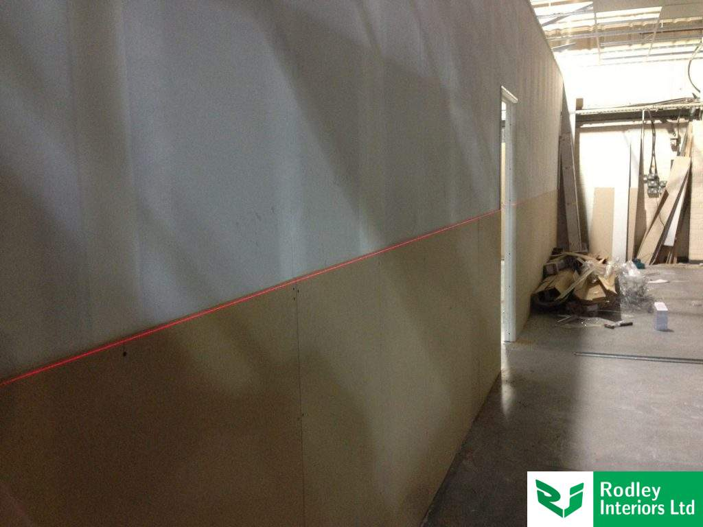 Laser line for levelling boards highlights the uneven floor.