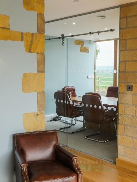Frameless glass partitions against stoneworl