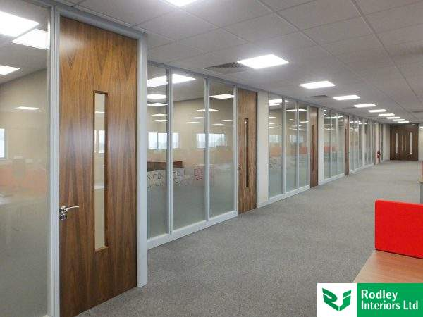 Lengthy run of formed offices and meeting rooms leaving a large open plan office area to the right.